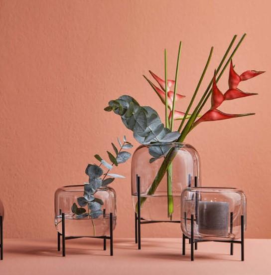 Drei gläserne Vasen mit Pflanzen und einer Kerze gefüllt vor einer roten Wand