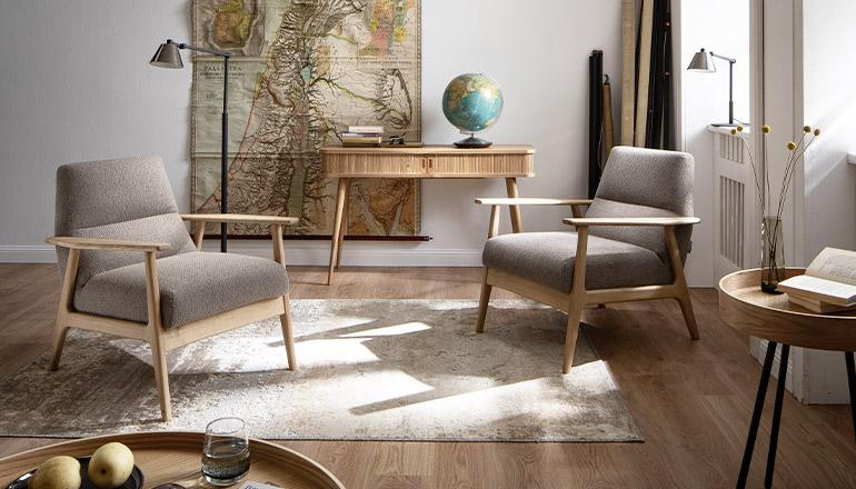 Zwei Sessel im Skandi-Stil auf einem Teppich vor einer Weltkarte, die an der Wand hängt