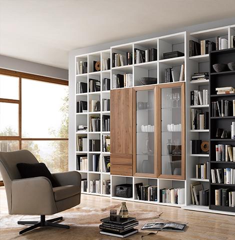 Weiße Wohnwand mit einem hölzernen Detail mittig und vielen Büchern vor einem Sessel