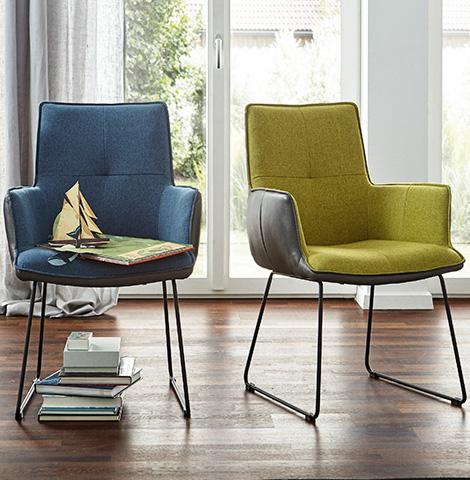 zwei-stuehle-mit-blauem-und-gelbgruenem-bezug-im-hellen-zimmer