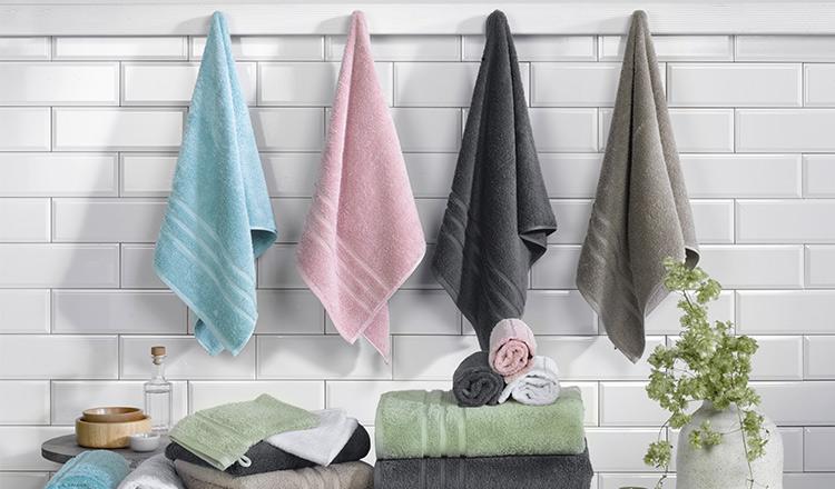 Vier unterschiedlich farbige Handtücher hängend vor einer weißen Wand