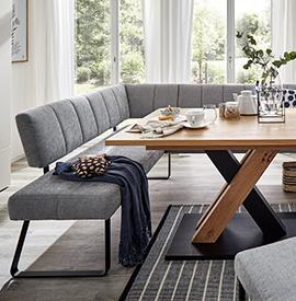 Graue Eckbank mit einer blauen Wohndecke an einem hölzernen Esstisch