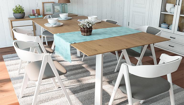 Sommerlich gedeckter massiver Esstisch mit türkiser Tischdecke und weißem Geschirr sowie weiße Esszimmerstühle