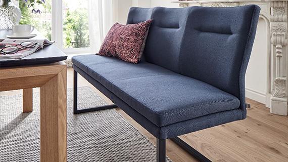 Blaue Sitzbank mit einem gemustertem Deko-Kissen neben einem Esstisch aus Holz