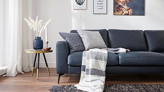 Blaues Sofa mit blauen Kissen und einer Wohndecke neben einem Beistelltisch