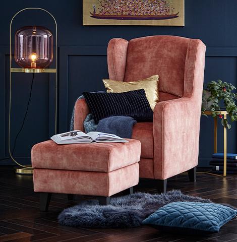 Sessel in Rosé vor dunkelblauer Wand auf dunklem Holzboden mit rosa Hocker