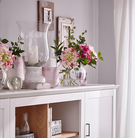 Rosa Vasen auf vanille-farbenem Highboard neben Blumen im Rosa-Ton