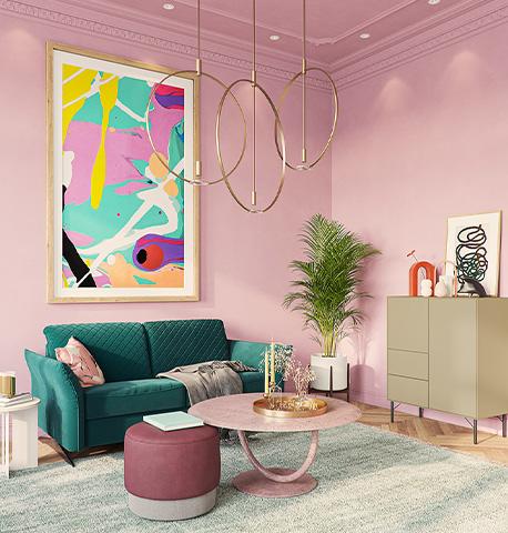 Dunkelgrünes Schlafsofa vor rosa Wand neben beigem Highboard und dunkelrotem Hocker sowie rosafarbenem Couchtisch