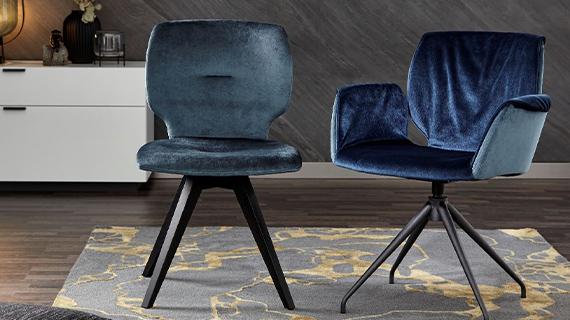 Zwei Stühle mit dunkelblauen Velourstoffbezügen vor einem weißen Lowboard
