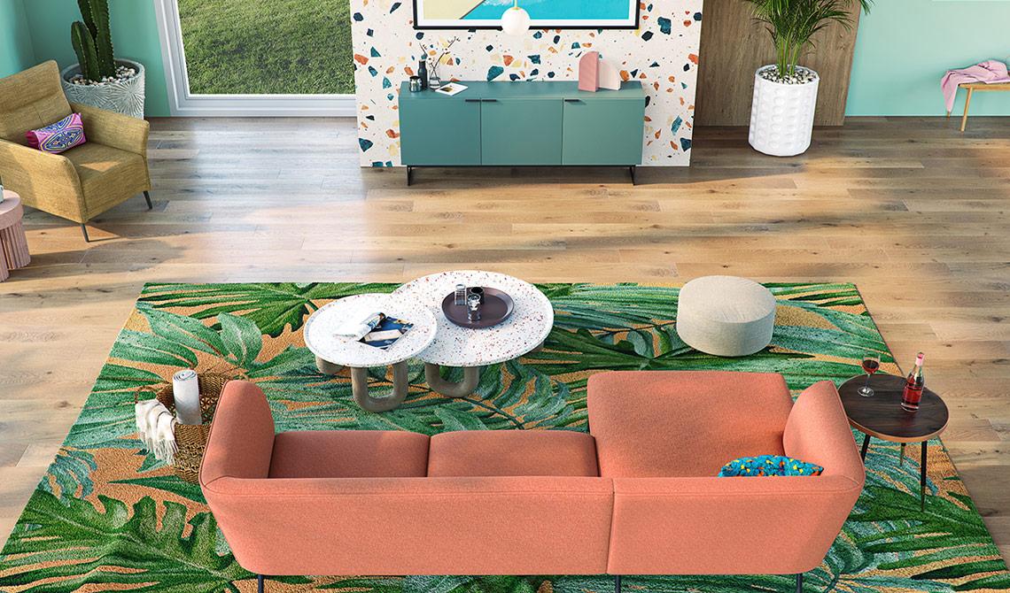 Pfirsichfarbendes Ecksofa auf Teppich mit Dschungelmuster vor gelben Sessel und mintgrünem Sideboard