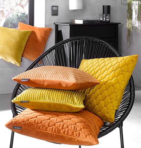 Moderner schwarzer Stuhl mit vier gestapelten gelben und orangenen Deko-Kissen