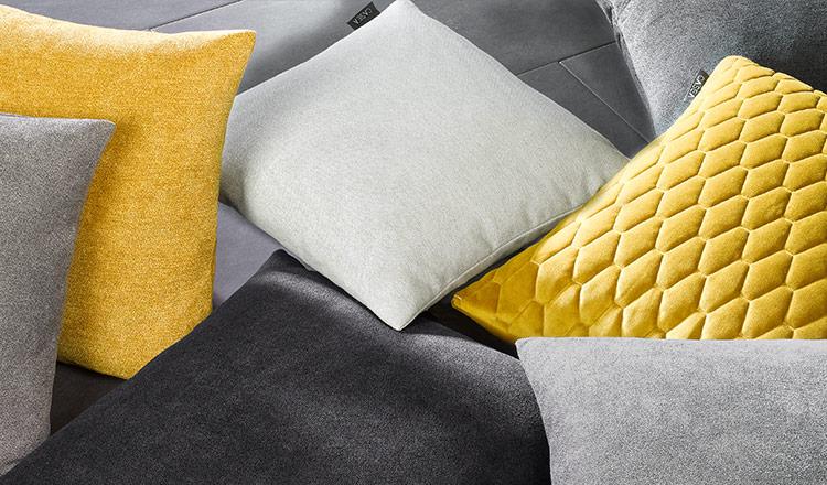Gelbe, graue, sowie je ein schwarzes und weißes Deko-Kissen auf einer grauen Ledercouch