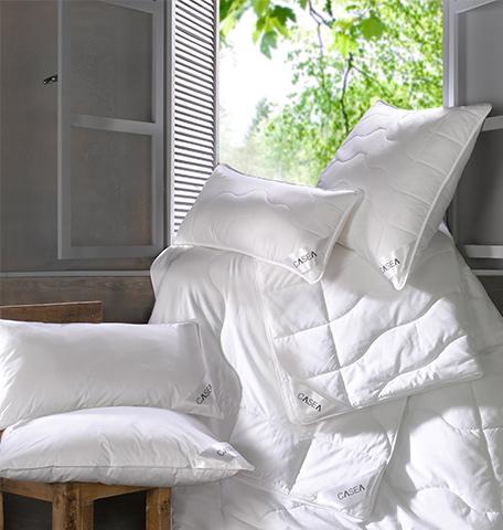 Bettdecken und Kopfkissen vor einem offenen Fenster und auf einem Stuhl