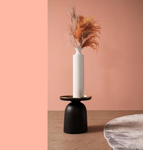 Schmale weiße Vase mit Trockenblumen auf einem schwarzen Sockel
