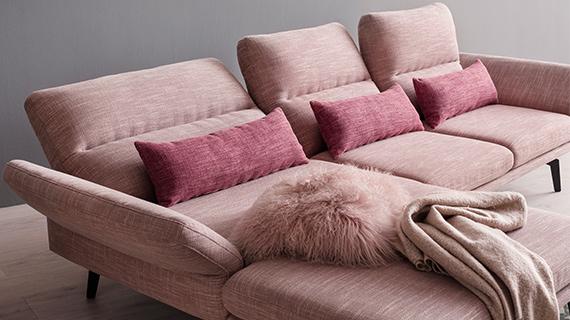 Rosafarbiges Funktionssofa mit Longchair und rosafarbigen Kissen sowie einer Wohndecke