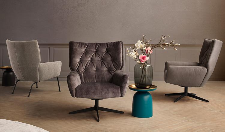 Drei verschiedene Loungesessel in Grautönen neben einer Vase