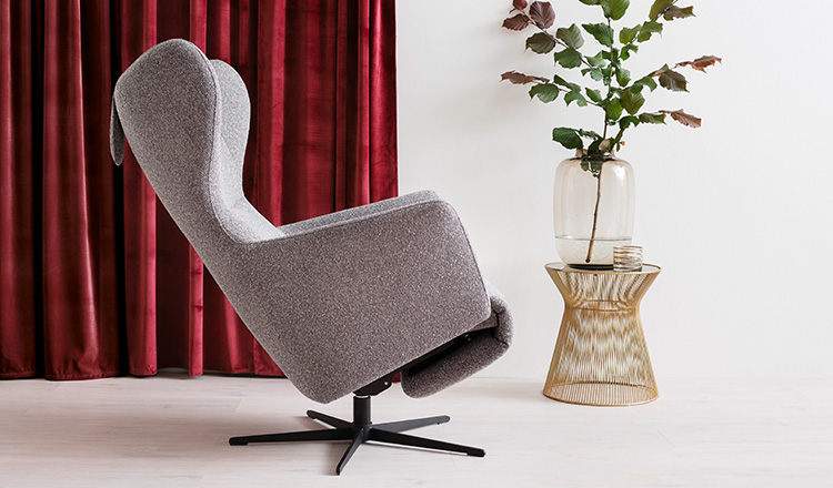 Seitliche Ansicht eines grauen Relaxsessels neben einem modernen Beistelltisch