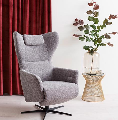 Grauer Sessel mit Relaxfunktion neben einem modernen Beistelltisch mit einer Vase