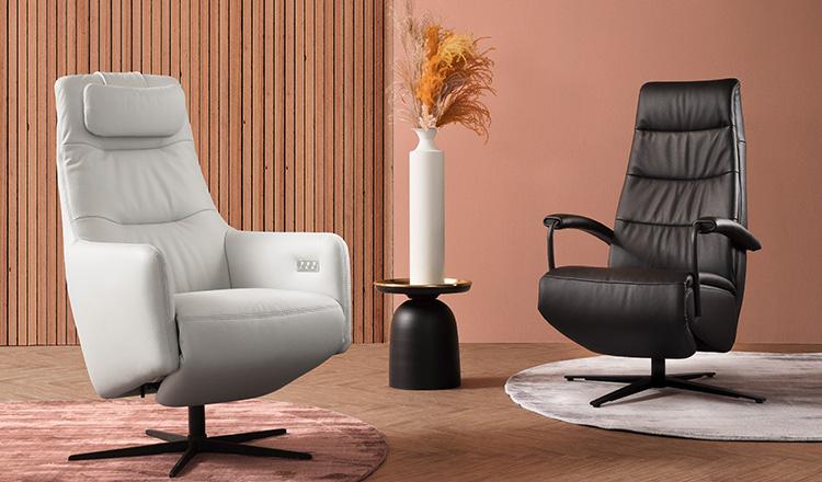 Ein weißer und ein schwarzer Relaxsessel aus Leder und eine Vase in der Mitte