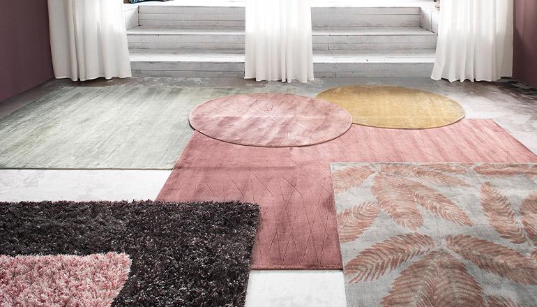 Viele Teppiche auf dem Boden in Gelb, Rosa, Schwarz und mit rosa Blättern gemustert