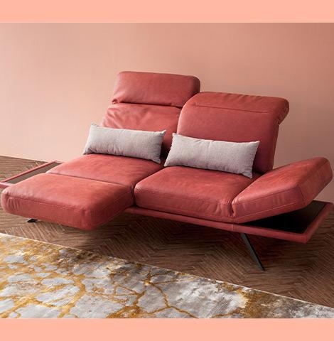 Rotes 2-Sitzer Sofa mit aufgebauter Relaxfunktion und zwei Deko-Kissen