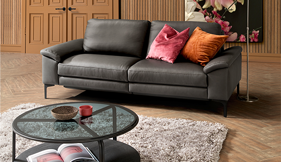 Ein graues 2-Sitzer Sofa mit bunten Kissen, einem Couchtisch und hellen Teppich