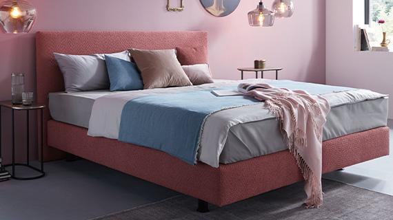 Boxspringbett mit amerikanischem Aufbau in Rosa und blauer und grauer Bettwäsche