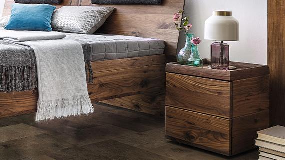 Dunkle Massivholzmöbel im Schlafzimmer aus Nussbaum: Bettgestell und Nachttisch