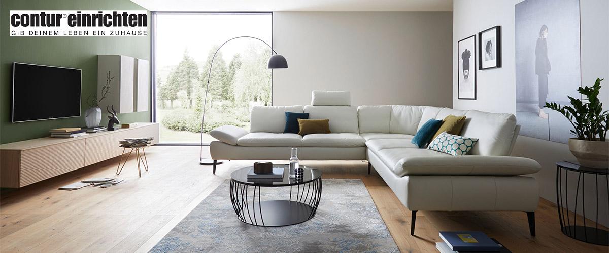 Weißes Ecksofa aus echtem Leder vor minimalistischer Wohnwand mit TV