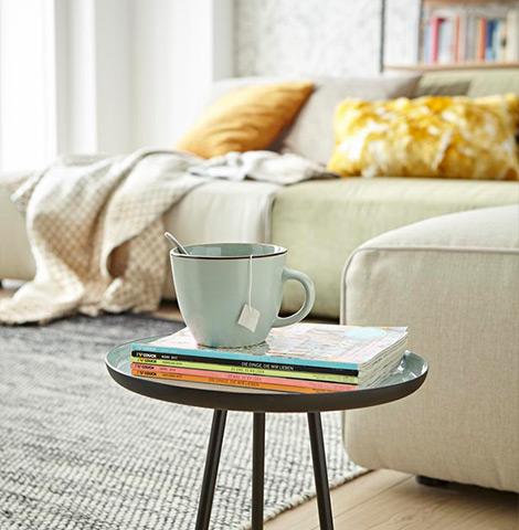 Runder Beistelltisch mit einer Tasse und Zeitschriften vor einem hellen Ecksofa