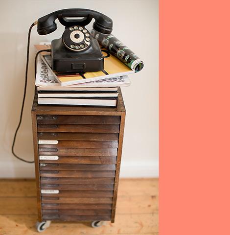 Altes, schwarzes Telefon auf Magazinen die auf einer alten Kommode aus Holz liegen