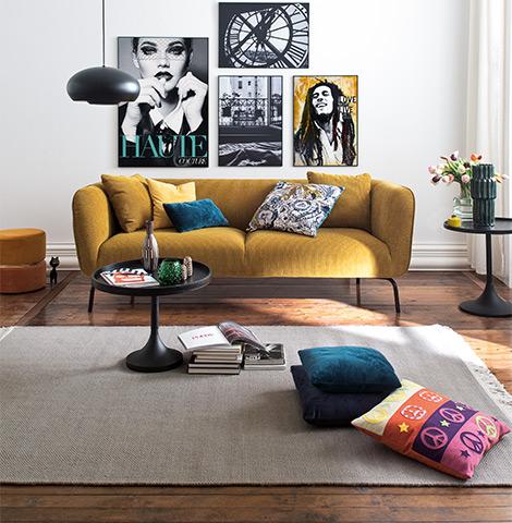 Senfgelbes Sofa aus Cord mit Kissen vor einer Wand mit vielen Posten