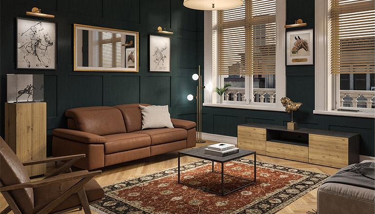 Lowboard aus Massivholz vor dunkelgrüner Wand mit cognacfarbenem Sofa und einer Holzvitrine mit Glaskasten