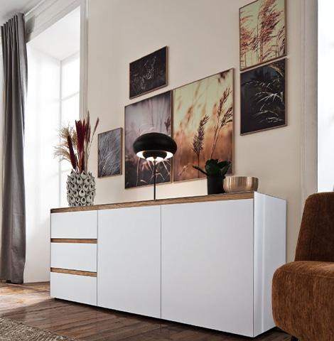 Weiße Kommode mit Griffen aus braunem Holz im natürlich eingerichteten Zimmer