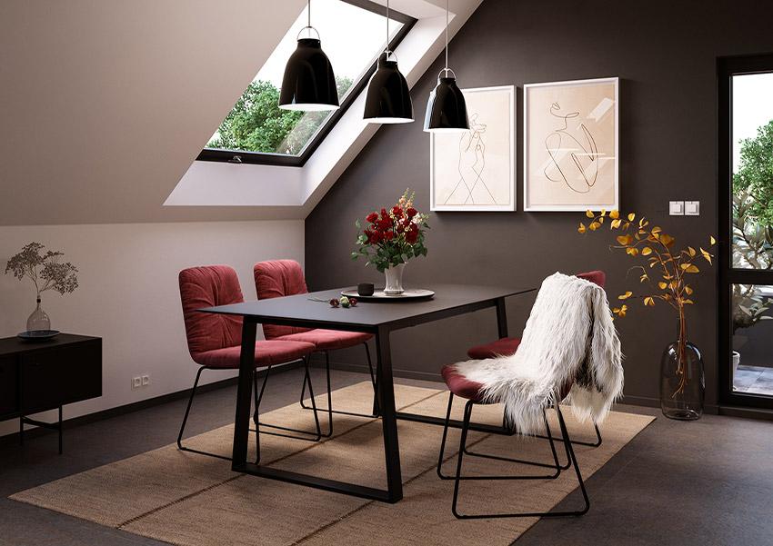 Schwarzer Esstisch mit dunkelroten Esszimmerstühlen unter einer Dachschräge