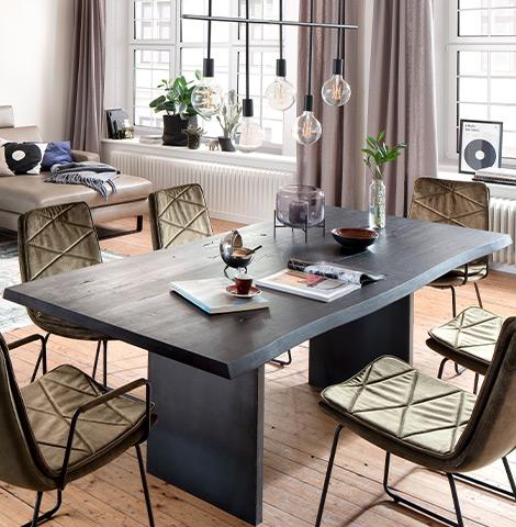 Schwarzer Esstisch aus massivem Holz neben dunkelgrünen Stühlen