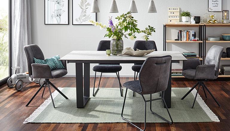 Esstisch mit modernem Kufengestell umgeben von grauen Esszimmerstühlen
