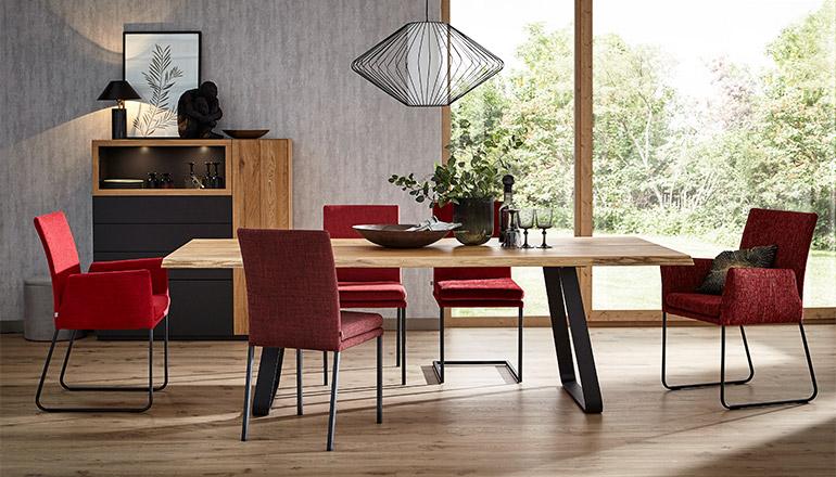 Fünf rote Stühle verteilt um einen Esstisch mit einer Tischplatte aus Massivholz