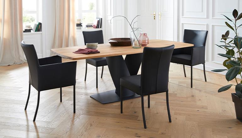 Esstisch aus Massivholz mit schwarzem Kreuzgestell und schwarze Lederstühle