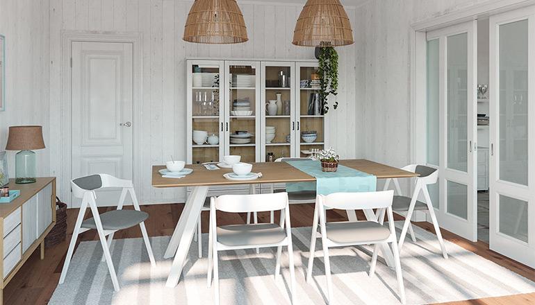 Weiße Stühle mit grauem Sitzpolster um einen Massivholztisch mit weißen Füßen vor einer hellen Vitrine