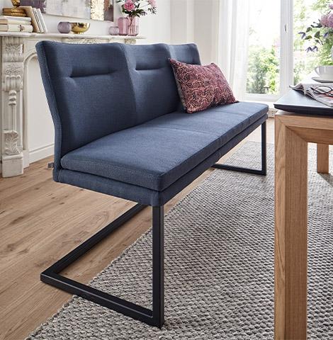 Tiefblaue Sitzbank mit Kufengestell vor einem Holzesstisch mit Dekokissen