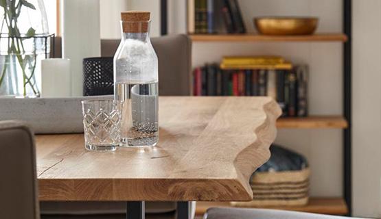 Eine Flasche Wasser und ein Glas auf einem Esstisch mit natürlicher Baumkante