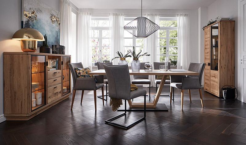 Esstisch aus Massivholz umgeben von hellgrauen Stühlen sowie einem High- und Sideboard