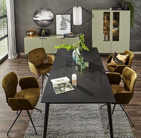 Grüne Vitrine und grünes Lowboard hinter einem Esstisch mit grünen Stühlen
