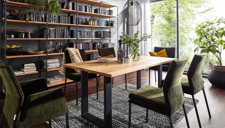 Grüne gepolsterte Stühle, die in einem natürlich eingerichteten Esszimmer mit Massivholz-Tisch stehen