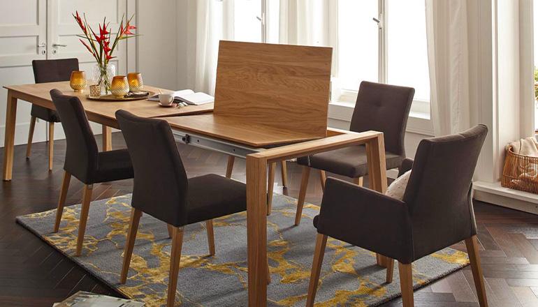 Ein Holz-Esstisch, an dem die erweiterbare Tischplatte gerade herausgefahren wird