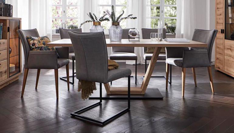 Graue Freischwingerstühle aus Leder mit schwarzen Füßen vor einem Esstisch aus Holz