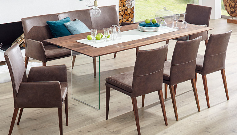 braune-lederstuehle-um-einen-grossen-esstisch-aus-massivholz