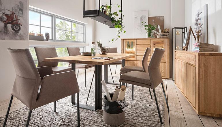 Beigefarbende Polsterstühle um schönen Esstisch aus Massivholz im modernen Esszimmer