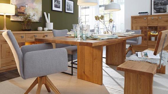 Esstisch aus Massivholz im Landhaus-Stil neben grauen Drehstühlen